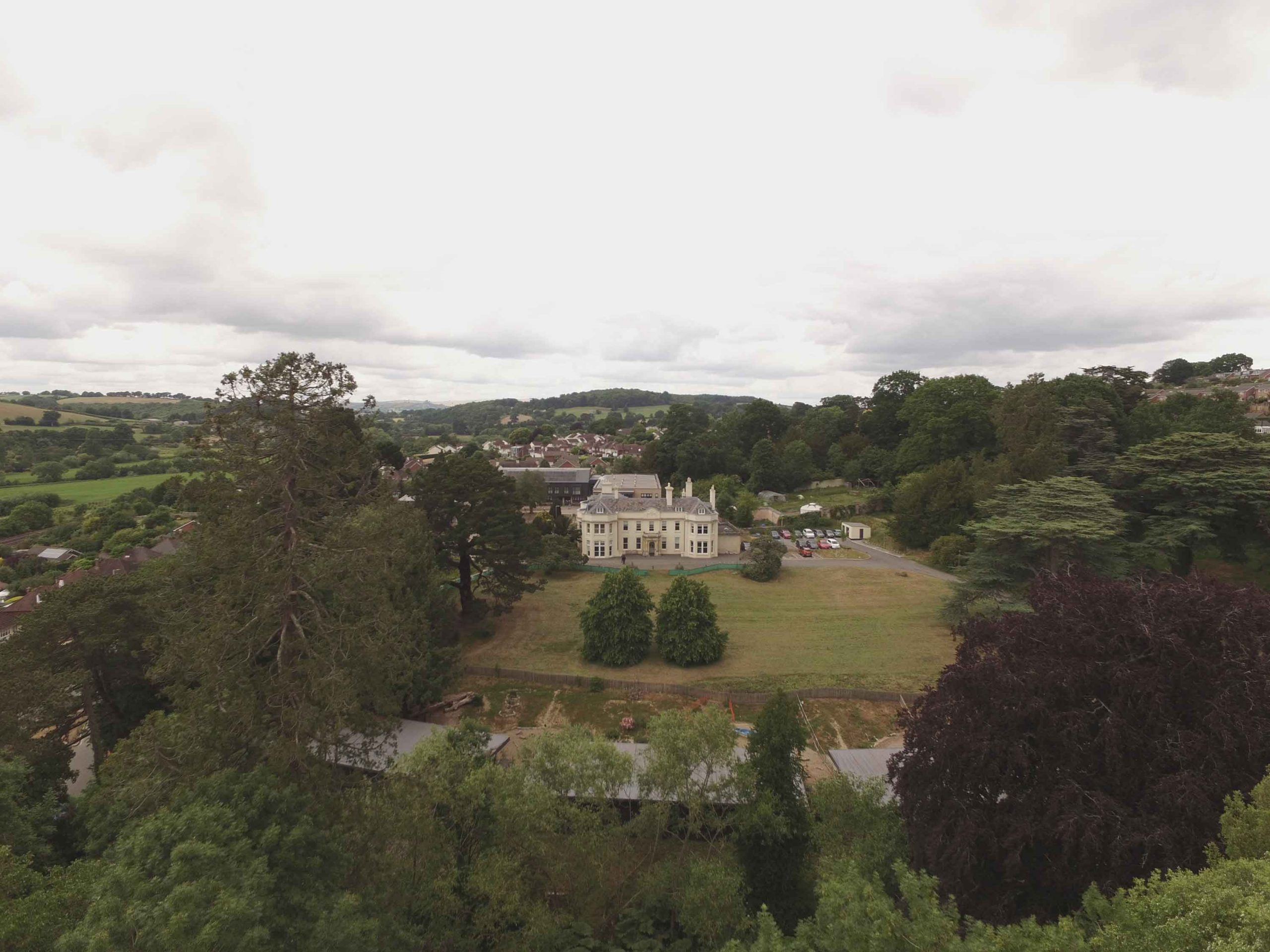 Arial photo of old double fronted building set in large grounds with grass and many trees - distant views of countryside