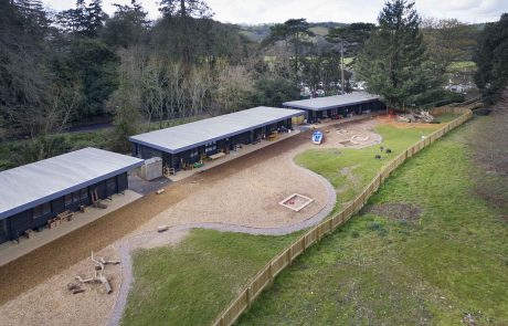 Arial shot of single storey wooden buildings with trees behind and woodchip play area in front